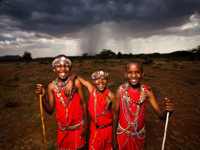 Masai in Najile, Kenya. A group of smiling boys in similar red clothes and headbands stand in a line in front of a dark sky and storm cloud.