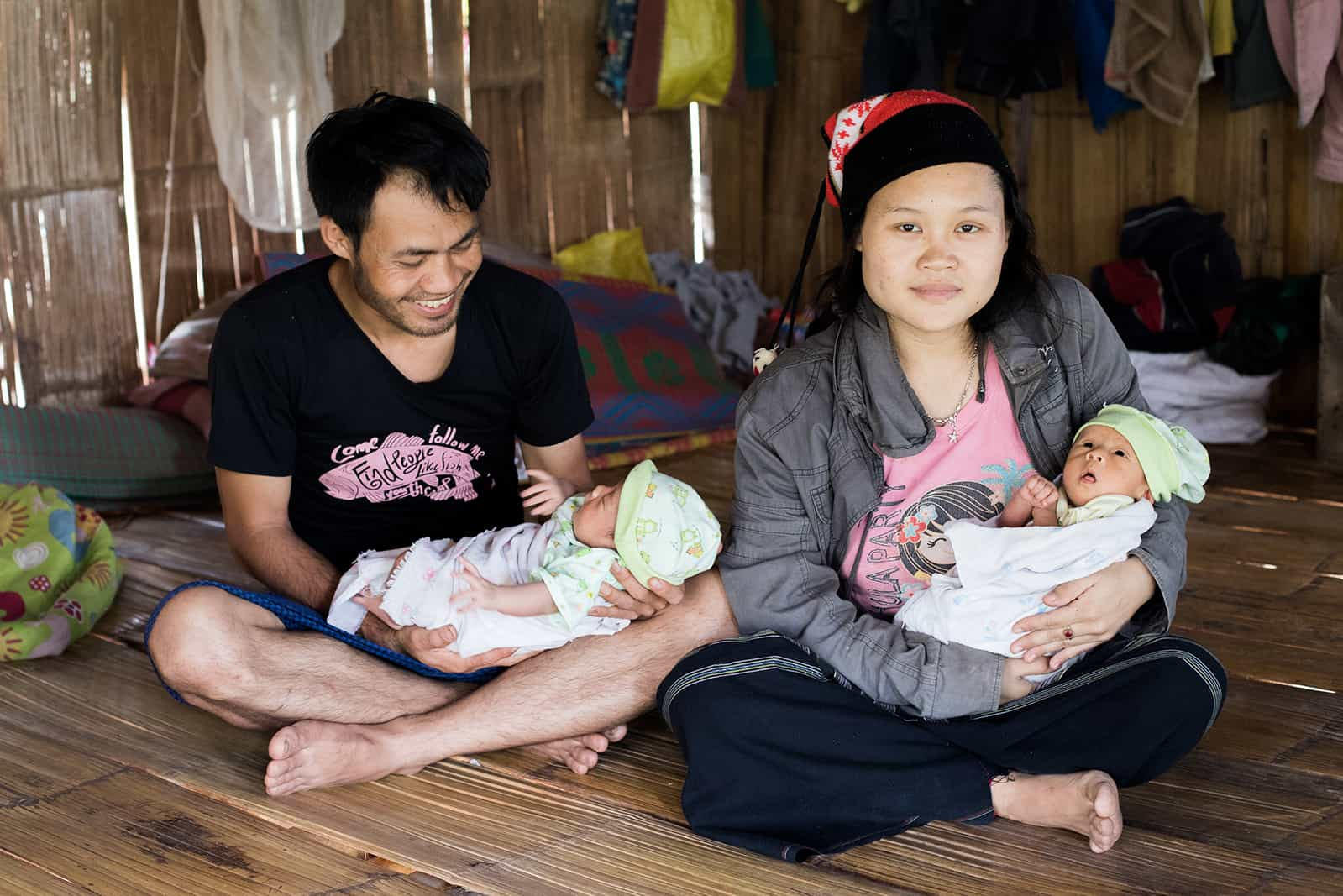 NoeDeMoo, Papala, and their twin baby girls, Phakaporn and Phakamon, sitting on the floor in their house. Papala is looking down at one of the twins smiling, and NoeDeMoo is looking at the camera.