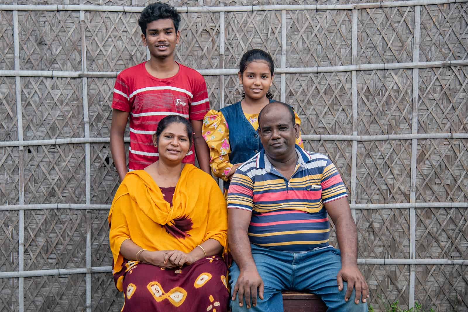 Sanjoy, in a red and white shirt, is with his family posing for a photo. His mother, in yellow, is sitting next to his father, Subhas. Sanjoy's sister is standing next to him. They are in front of a bamboo wall.