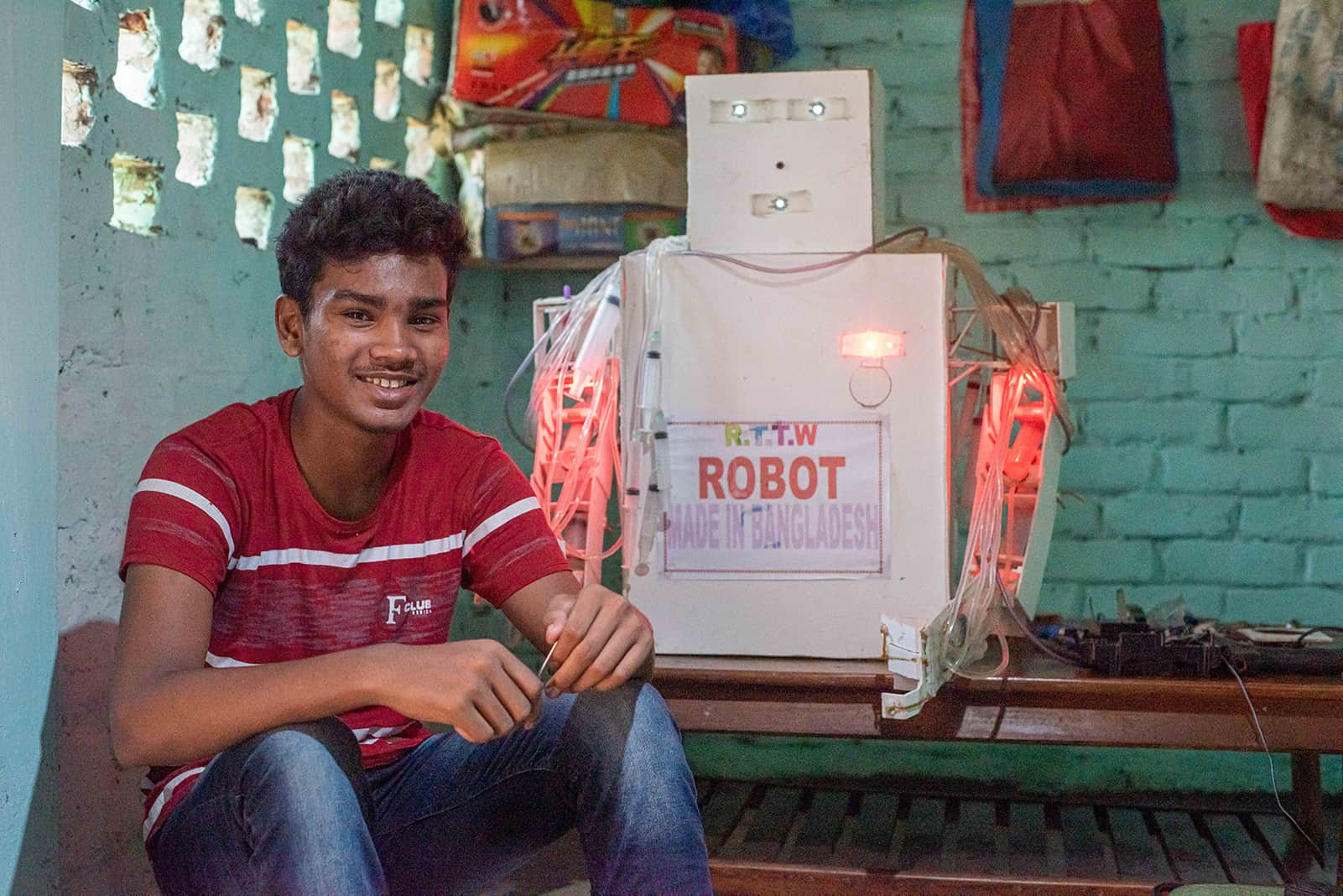 Sanjoy, in a red shirt, is sitting in front of the white cardboard robot he made for the science fair, where he came in second place.