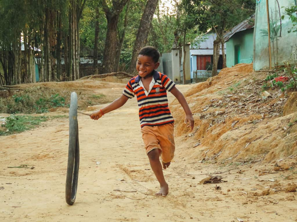 Boy wearing orange shorts with a red, blue, and white striped shirt. He is running down a dirt road with a bicycle tire and a stick.