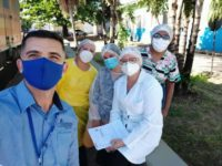 A man and four nurses wearing personal protective equipment look at the camera