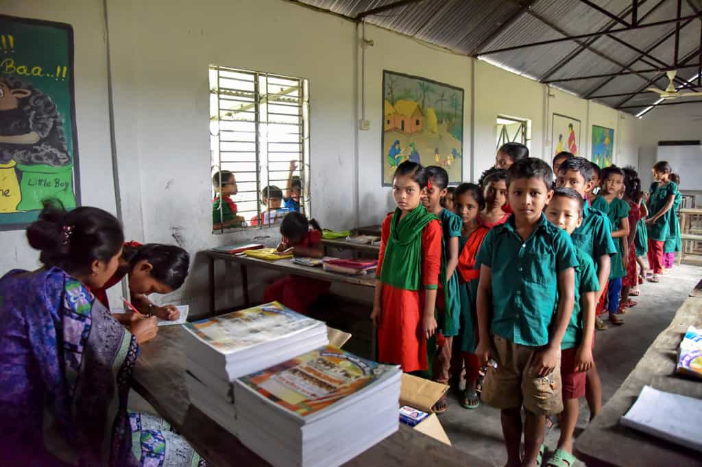 Children, most wearing red or green school dress or shirt uniforms, stand in two lines, facing towards a teacher's desk.