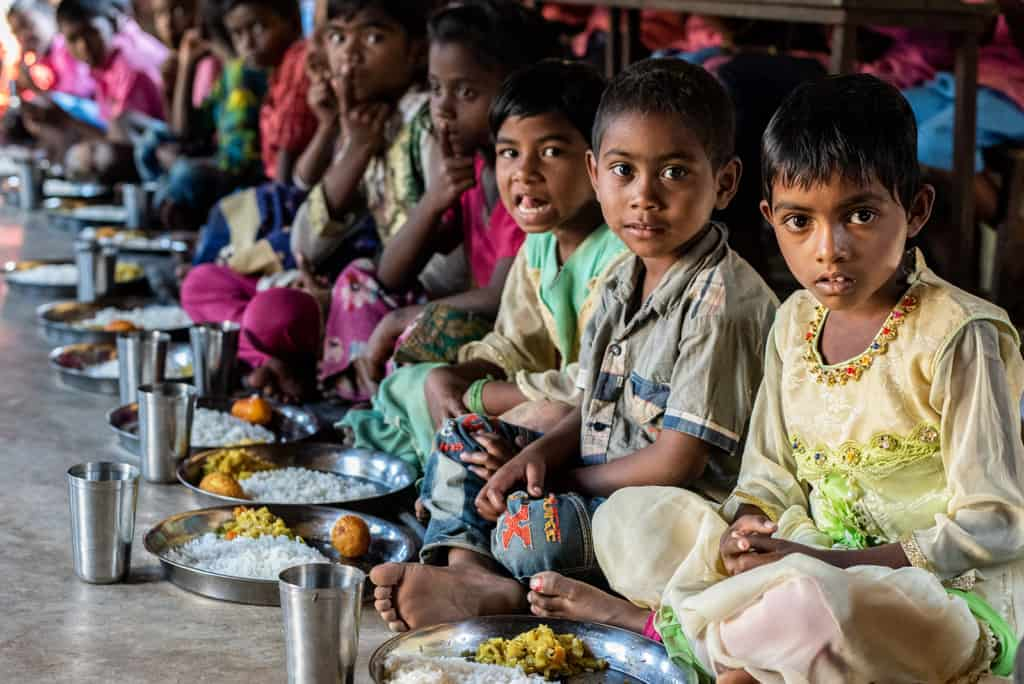 The children are waiting for their food at the project. The children wait until everyone is served before they begin eating.
