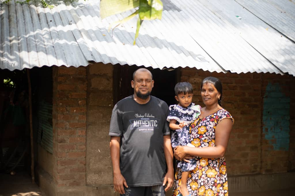 Densy is wearing a blue and white dress. She is being held by her mother, Jemalini, wearing a blue, white and yellow dress. Her father, Jenishtan, is standing beside them in front of their house which was submerged in three feet of water during the flood.