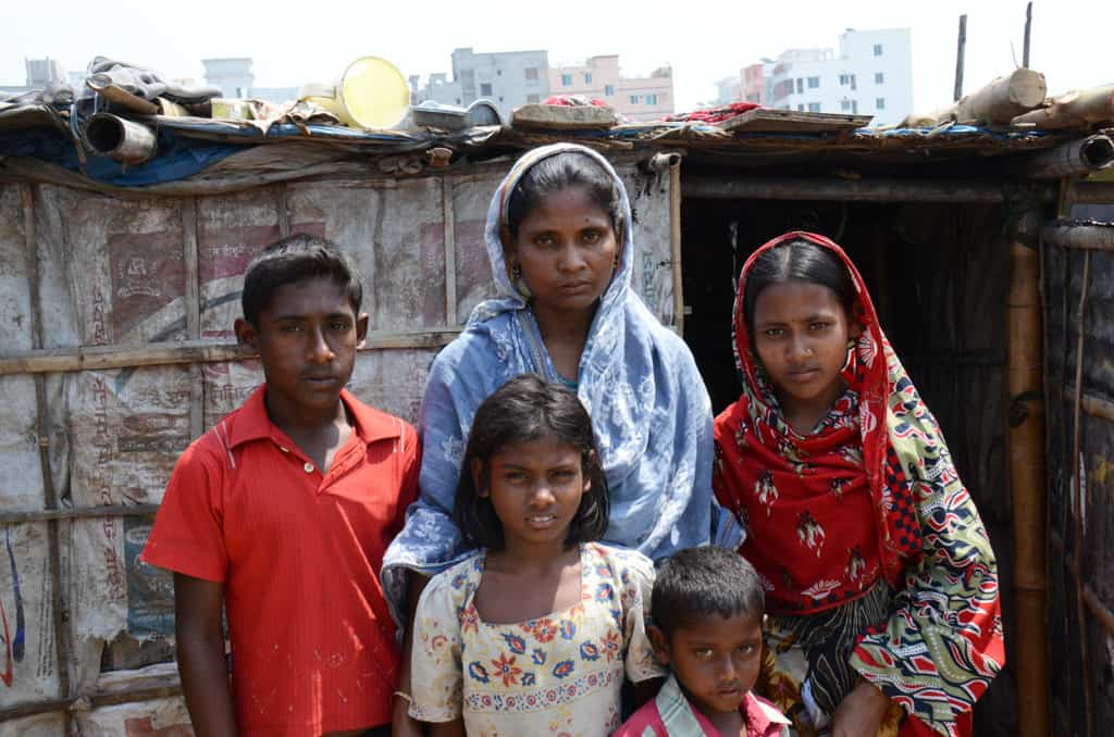 Family in the slums wearing traditional clothings. High rise buildings are in the background.