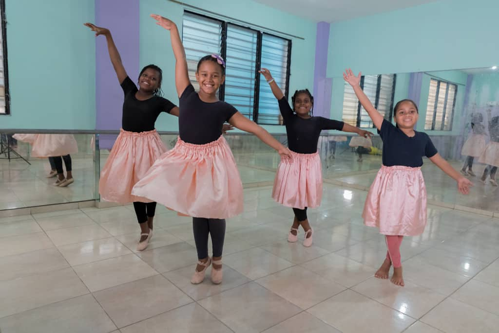 Four girls making eye contact and smiling while doing a dancing pose and smiling at the camera. They are all wearing black tee shirts, coral dancing skirts and light pink ballerina dancing shoes.