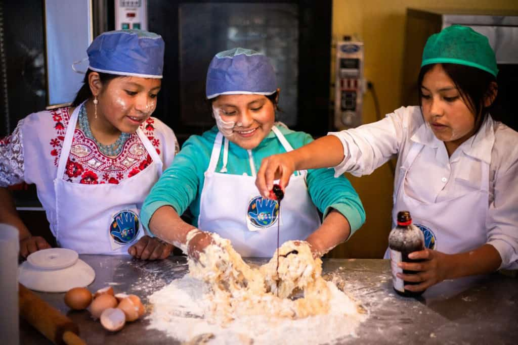 three young ladies mixing dough