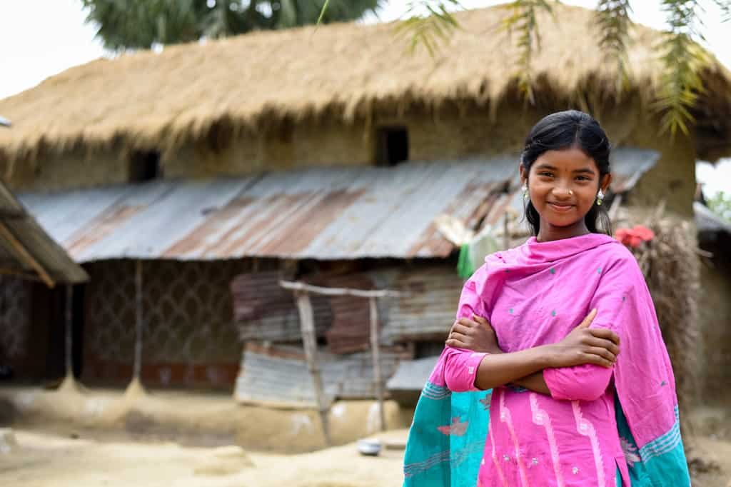 A girl wearing pink and blue clothing in front of her home made of corrugated metal, grass, hay and repurposed materials. Her arms are crossed.