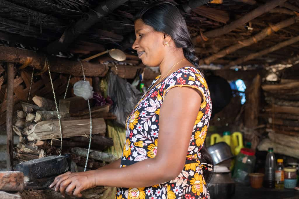 Jemalini is wearing a blue, white, and yellow floral dress. She is cooking in her kitchen on the top of a barrel. Behind her, there is firewood used for cooking tied up to the wall so it will not get wet.