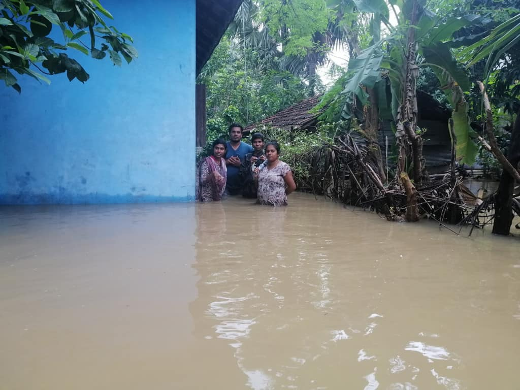 Four Compassion staff members are waist deep in water outside a blue building. They are going to meet Jenishtan and his family after the flood.
