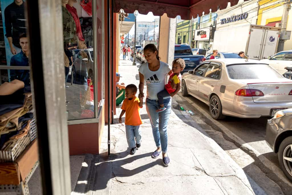 A boy, wearing an orange shirt, walks down the sidewalk with his mother, who is also carrying another child in her arms as they go shopping at the store and market.