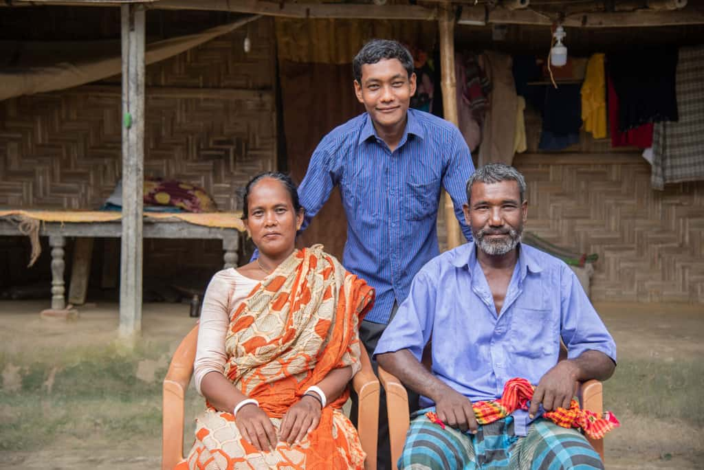 Lipon is wearing a blue shirt and gray pants. He is with his parents in front of their mud hut.