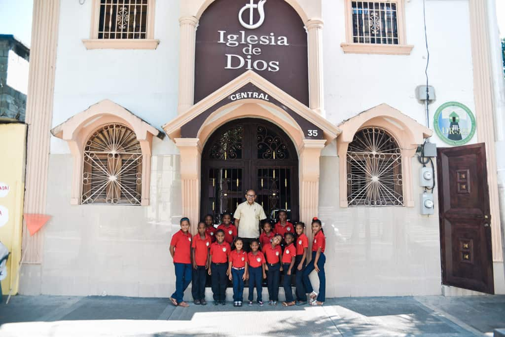 A pastor in a beige shirt standing in front of his church surrounded by children wearing red polo shirts.