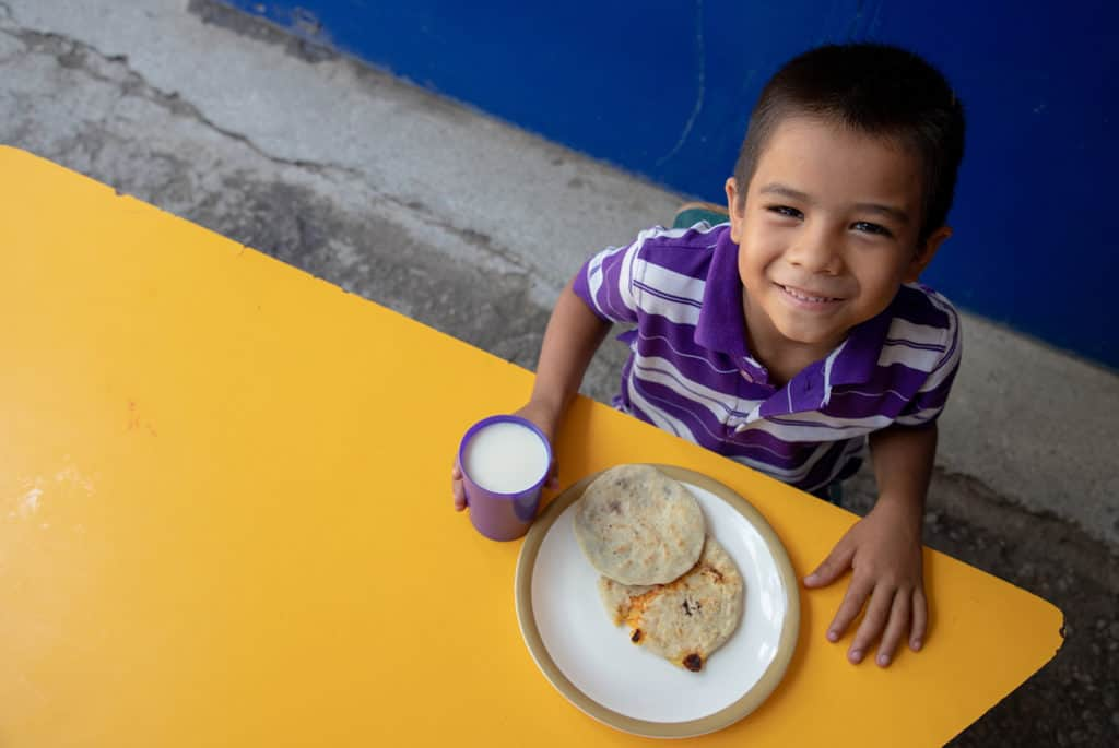 Smiling boy wearing a purple and white striped shirt sitting at a table with Pupusas and a cup of milk
