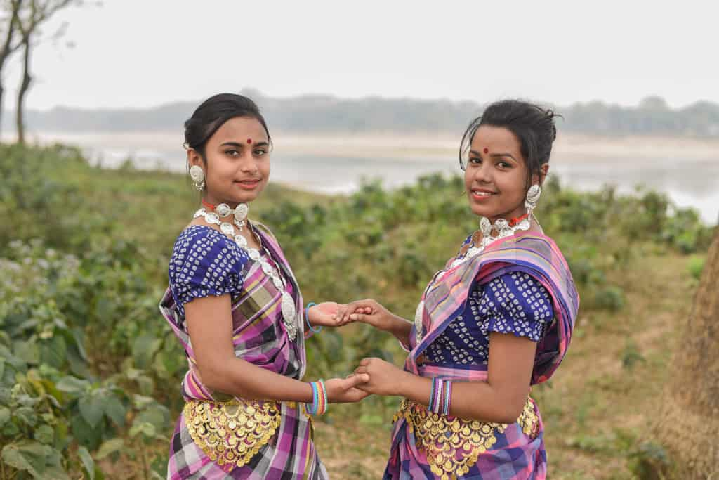 Two women standing in front of a small river and are dressed in colorful traditional clotihgin
