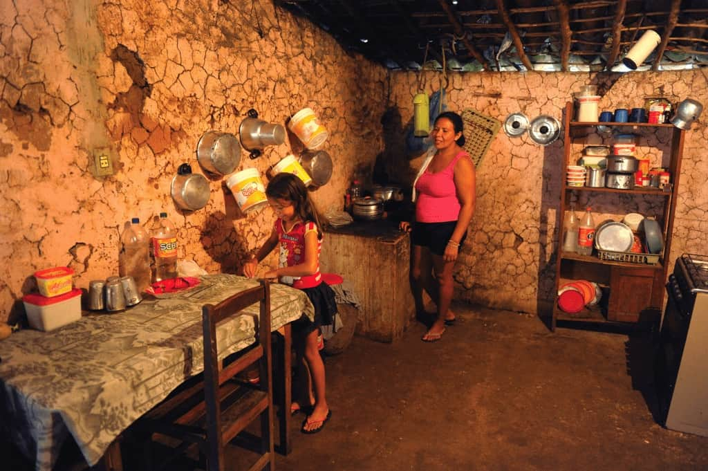 A woman and a girl in a kitchen of a home. The girl is cleaning off the table. Pots and pans hang on the clay walls
