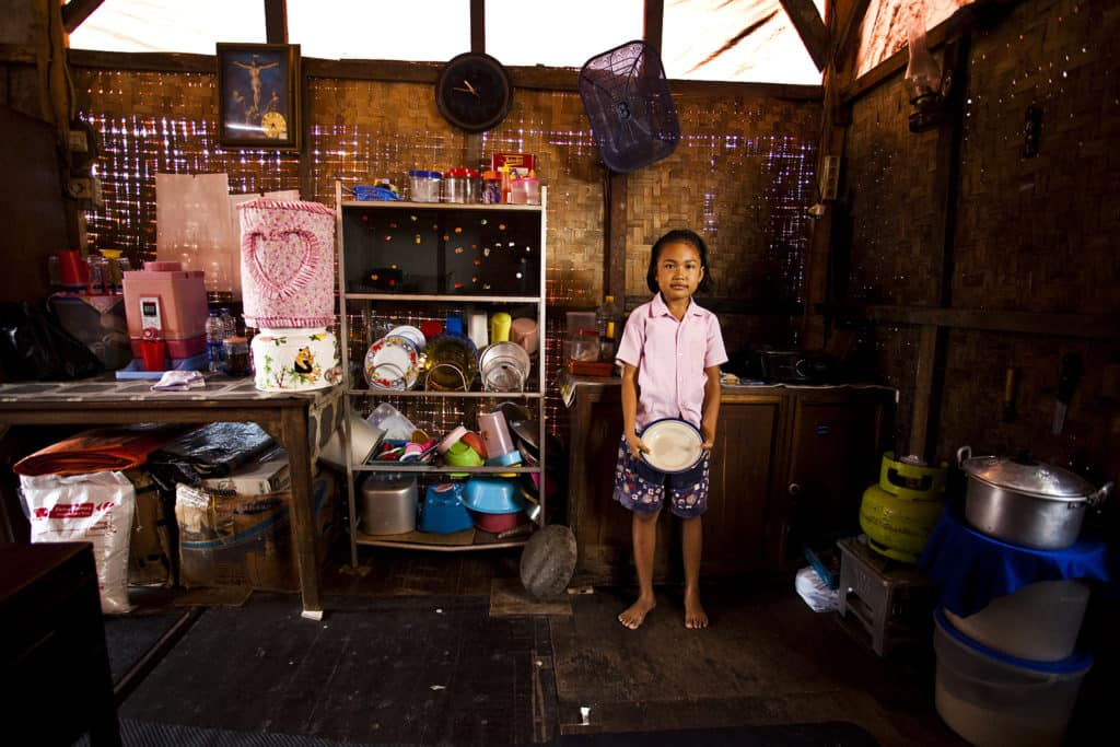 A girl wearing a pink shirt holds a clean dish. She is standing next to a rack of neatly organized dishes in a kitchen that has bamboo walls.