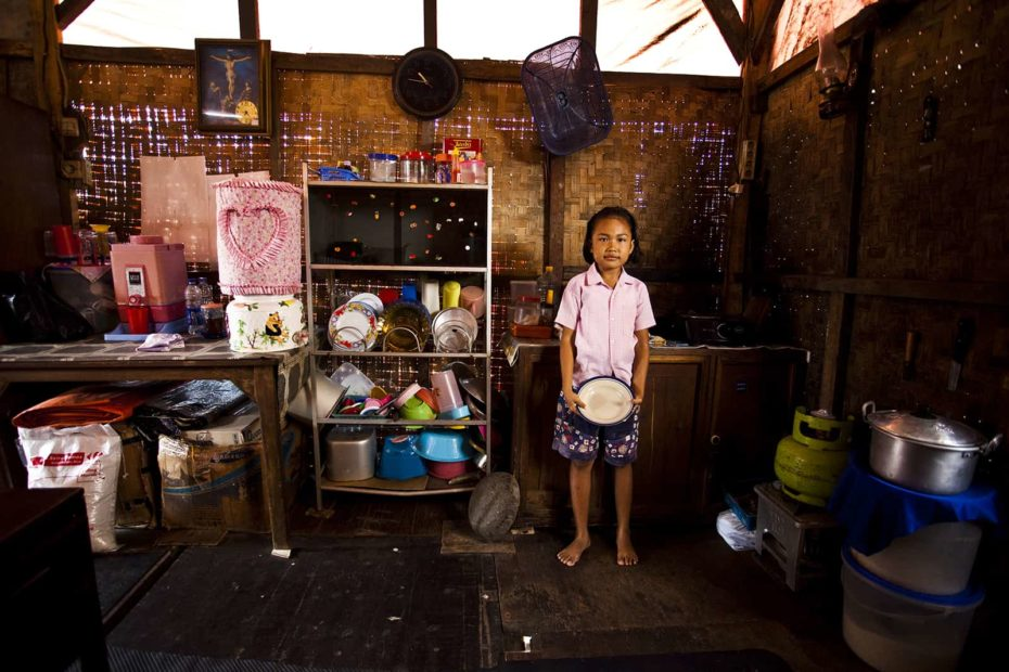 A young girl wearing a pink shirt holds a dish and looks at the camera. She is in her family's kitchen, which has bamboo walls and a shelf of organized dishes.