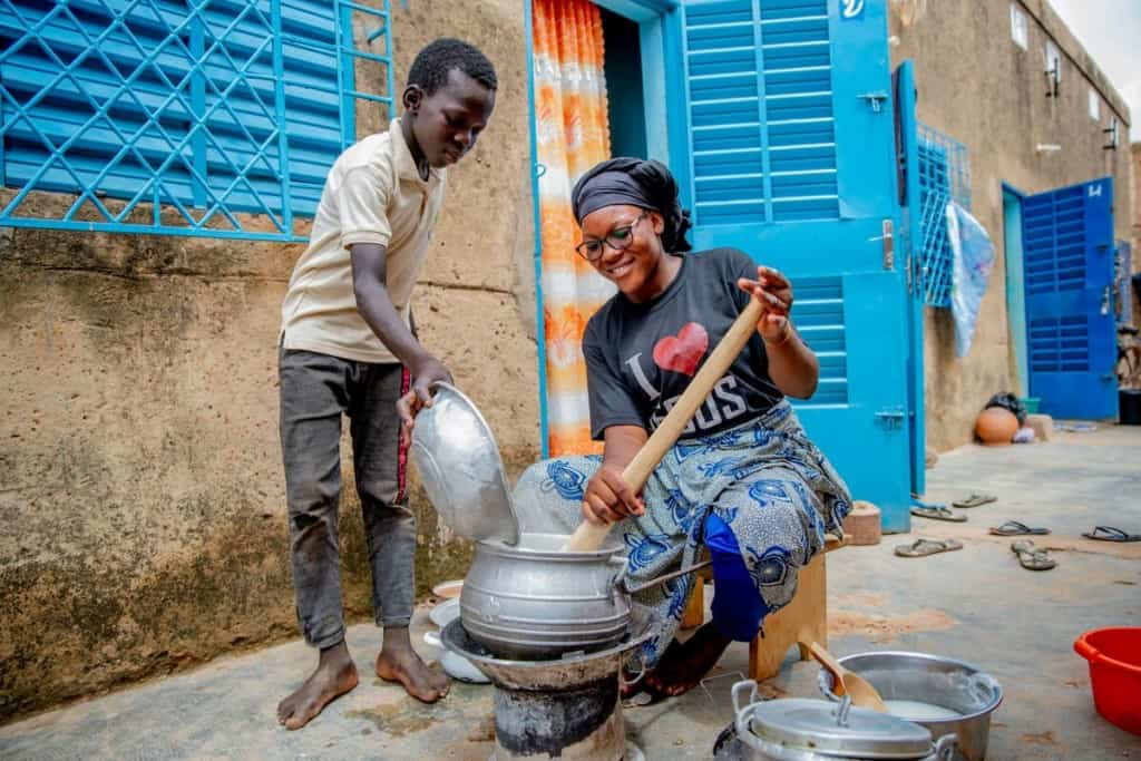 A boy pours an ingredient from a metal pan into a metal cooking pot, which a woman stirs over coals.