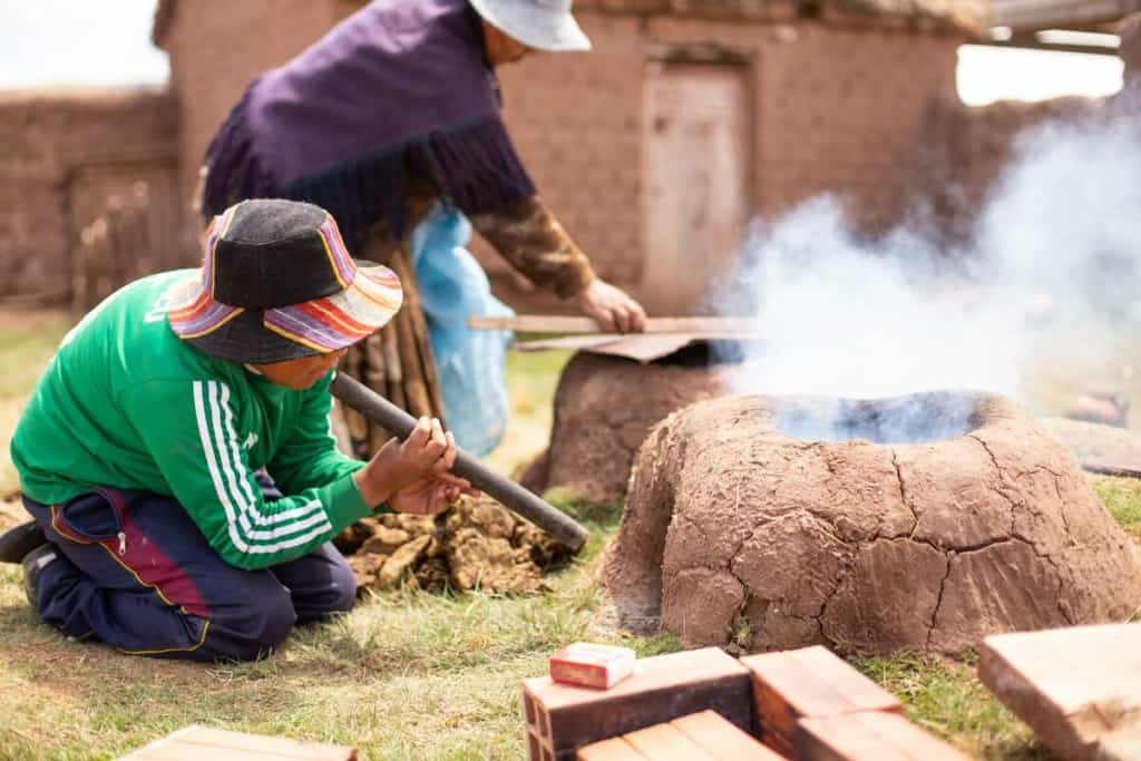 A Bolivian boy blowing air into a small clay oven or stove as smoke rises from it in the outdoor kitchen. A woman prepares another oven in the background.