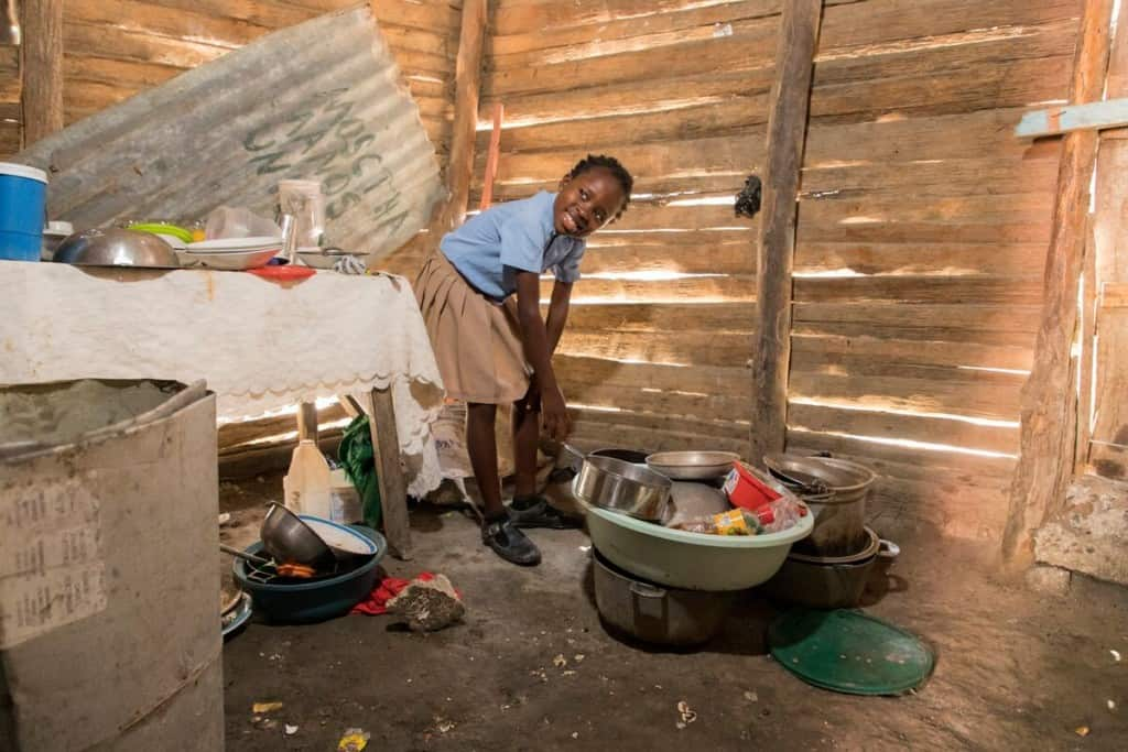 A girl in a wooden home leans over a bucket of dishes