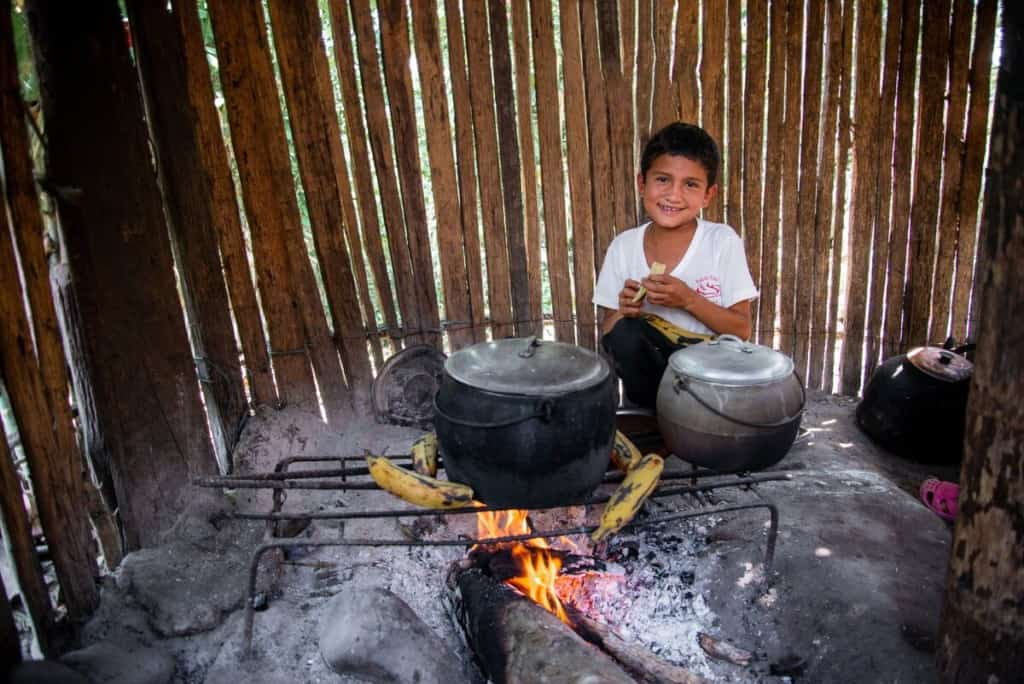 A young boy in Peru sits behind two large iron pots over a firepit in a home, peeling a plantain.
