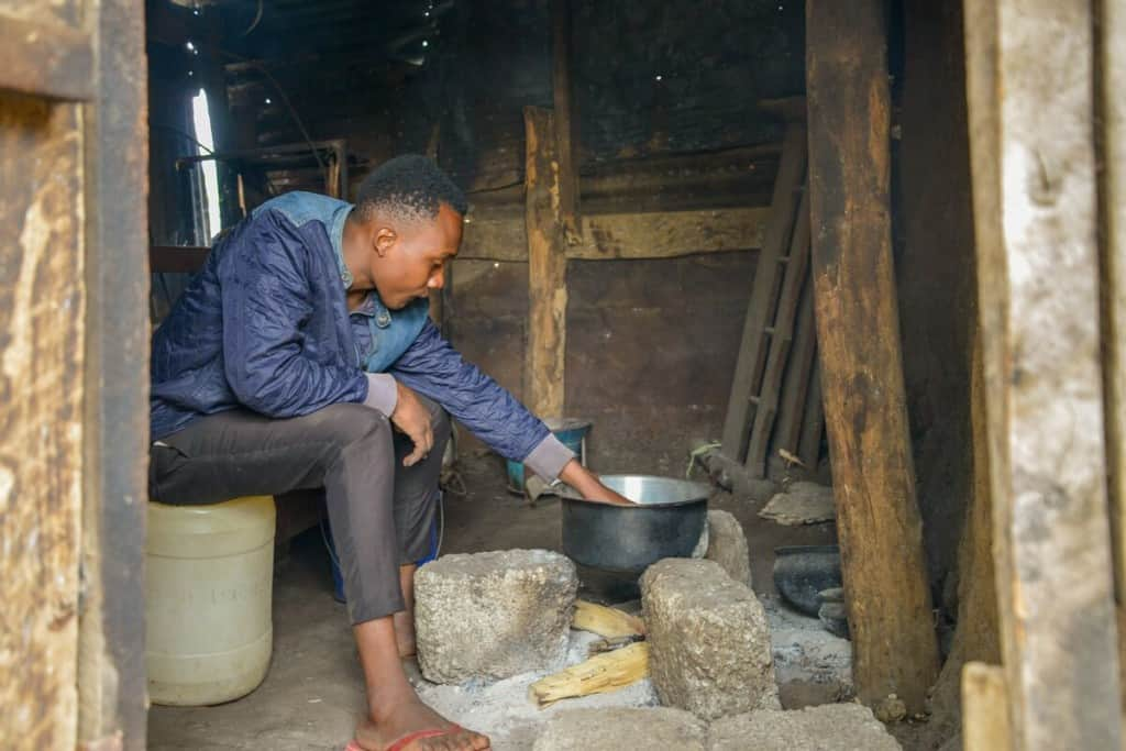 A young man sits on a plastic container inside a small home with his hand in a metal cooking pan. The pan is set over an unlit fire pit.