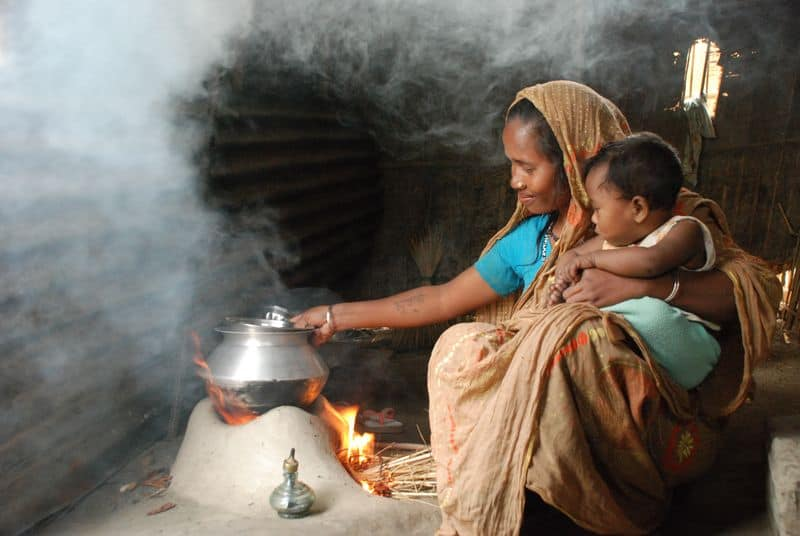 A woman wearing a blue shirt and a long piece of colorful fabric over her head and body holds a baby as she heats a metal pot over a fire. Smoke rises around them in the dark indoor space.