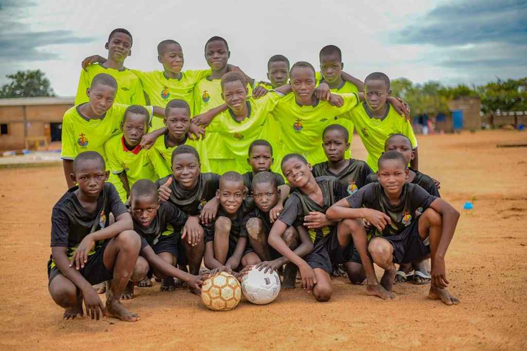A group of boys posing with smiles and soccer balls.