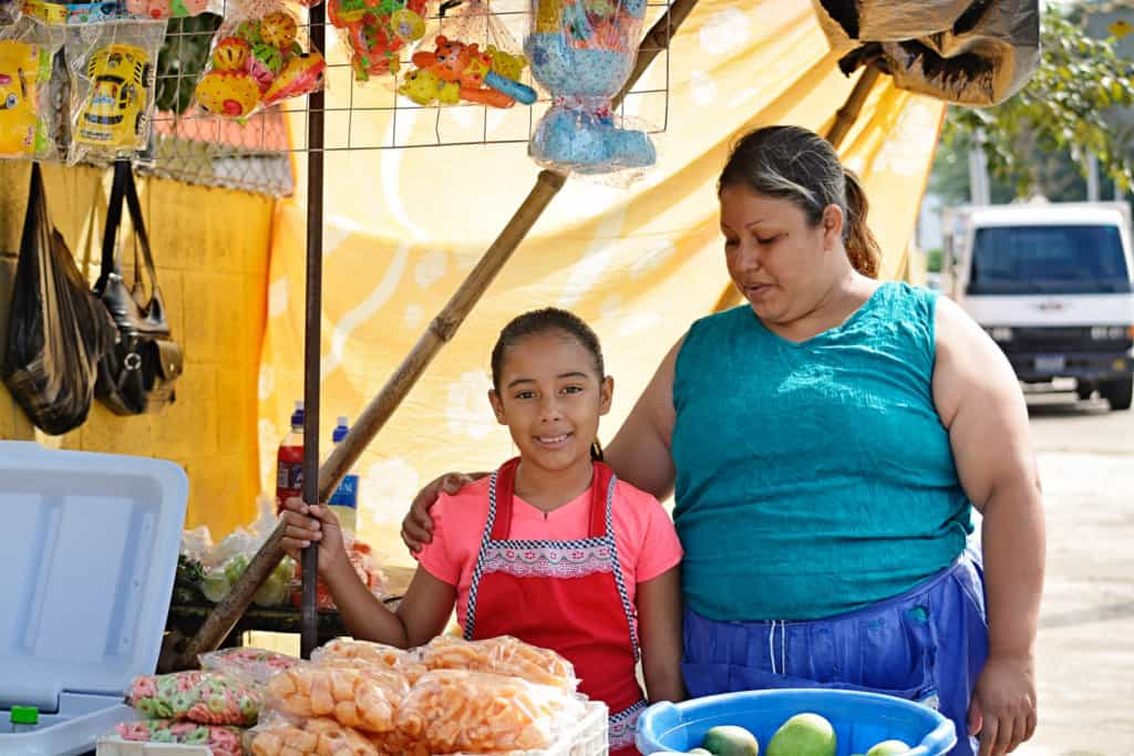 A girl wearing a pink shirt and red small apron smiles standing besides her mother who is wearing a sleeveless blue tank shirt at their small food open market stall selling fruits, homemade food, and drinks.