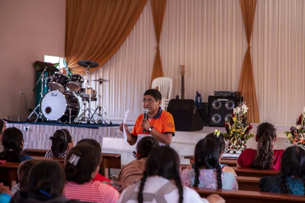 A man, in an orange shirt, holds a microphone and stands in front of a group of women sitting in pews. There is a stage with a drum set behind him.