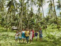 Happy, smiling, laughing children, boys and girls, males, females run outside in the grass surrounded by tropical, palm trees wearing blue, yellow shirts, white shorts, blue and white dress.