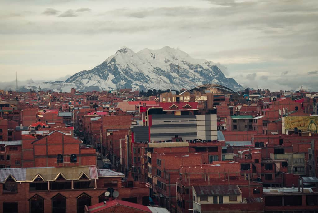 Brown brick buildings are in the foreground and a tall snowcapped mountains rises in the background  in the city of El Alto, La Paz.