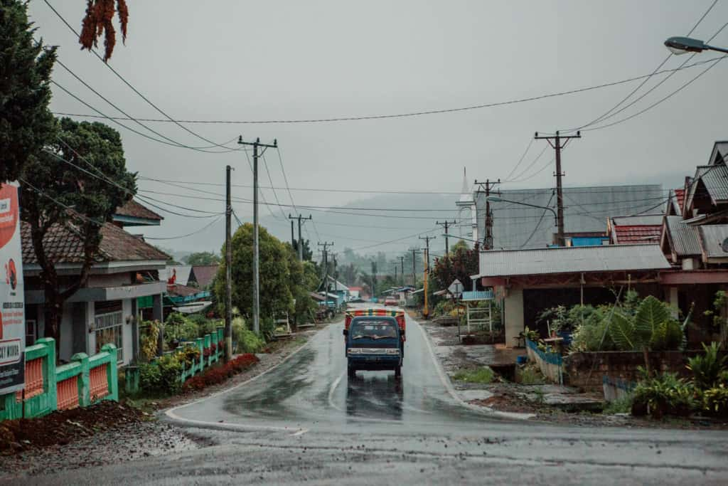 Truck driving on a wet street through a small town in Indonesia.