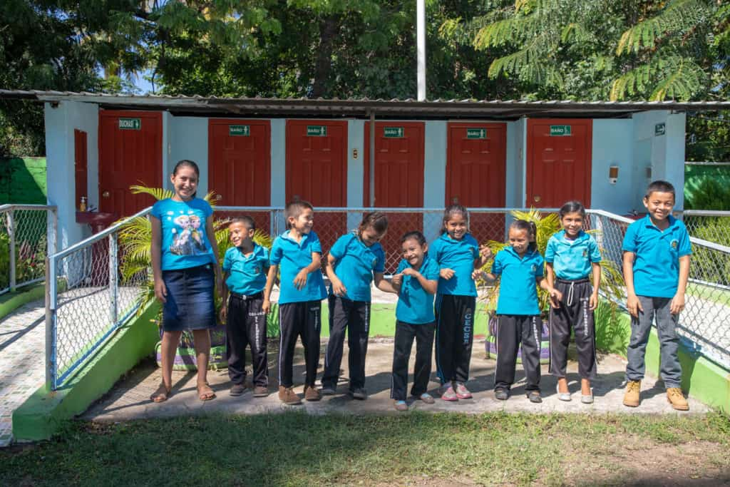 A group of beneficiaries, all wearing blue tee shirts, laughing and smiling all together. Behind them are the new restroom facilities with the first toilets in the community that flush with water.