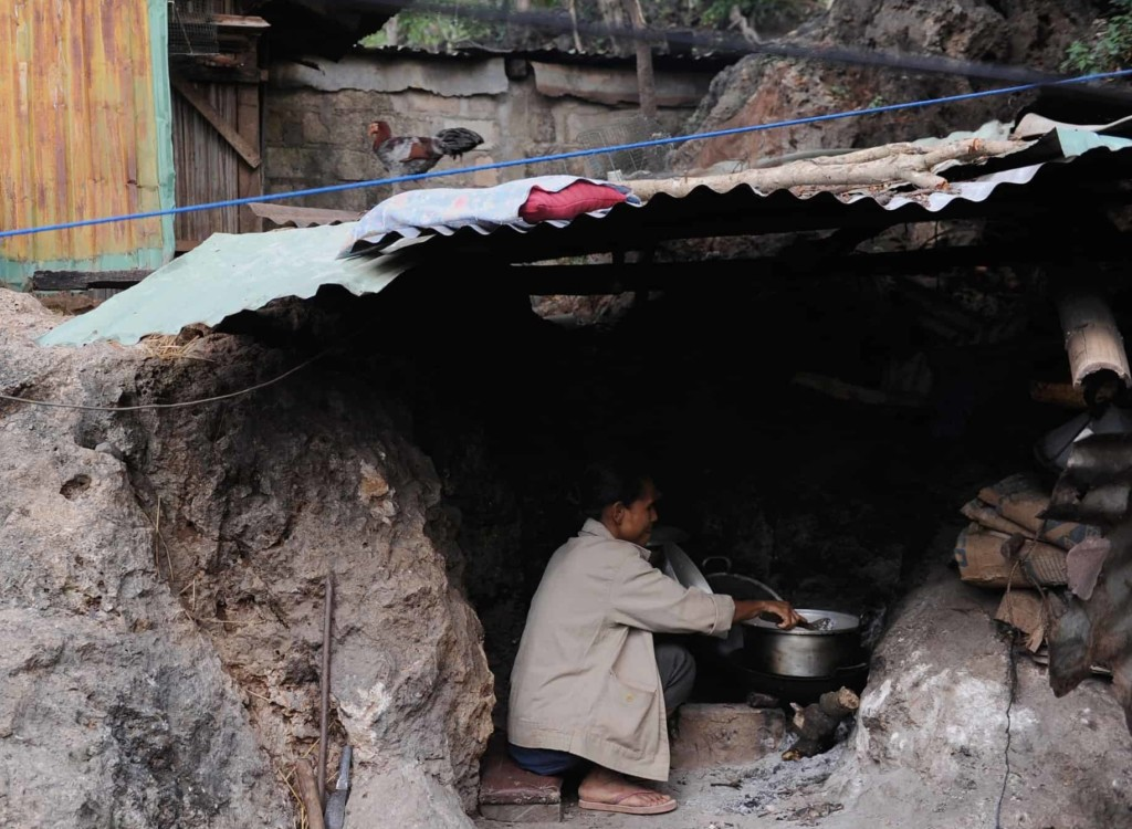 A woman sits cooking in a pan in a kitchen dug out from a hillside, covered in a sheet of tin.