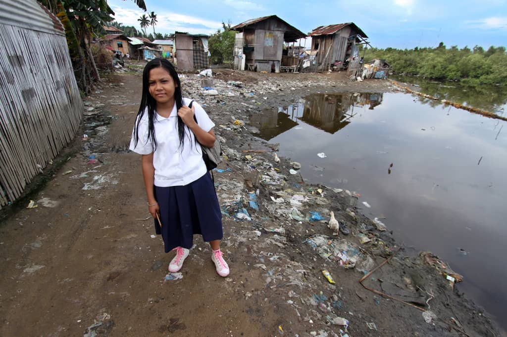 Girl wearing a white shirt, walks through her neighborhood and community, dirt road beside poor poverty homes, on her way to school. She is walking beside a water filled stagnant unhealthy unsanitary, pool of polluted water with garbage and trash strewn along the dirt road.