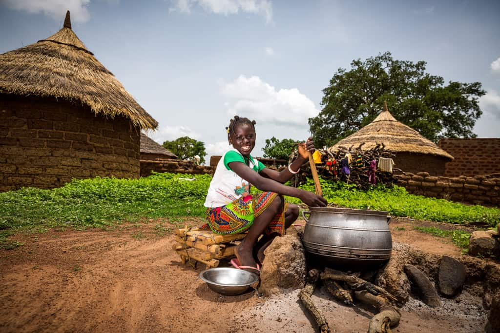 Girl sitting on a pile of firewood while stirring with her hands and meal preparation cooking making food.
