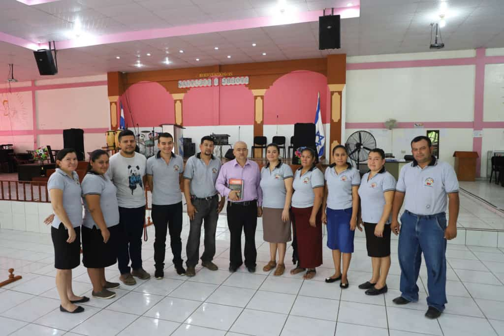Pastor Pedro Segovia and the Church's staff are in the sanctuary. Most of them wearing a grey polo shirt and Pastor Pedro is wearing a purple button-down shirt. The background is the altar where the Pastor preaches to the congregation and the worship band leads.