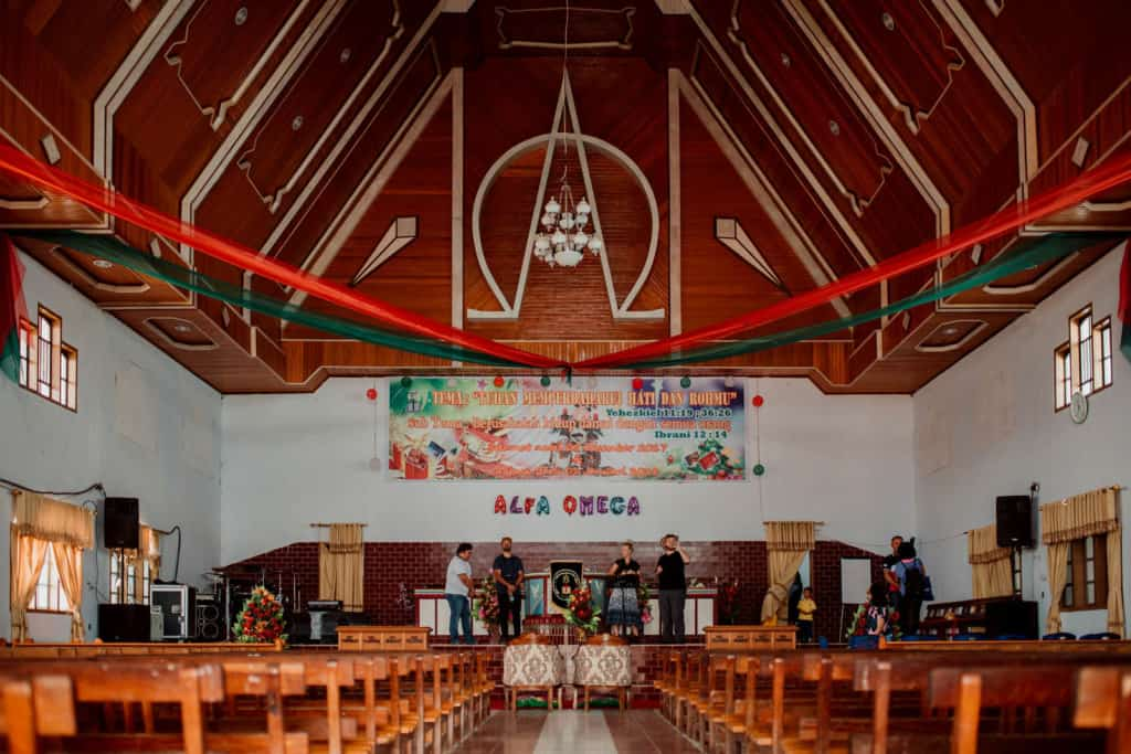 The inside of a church with wooden pews. There are people on the stage.
