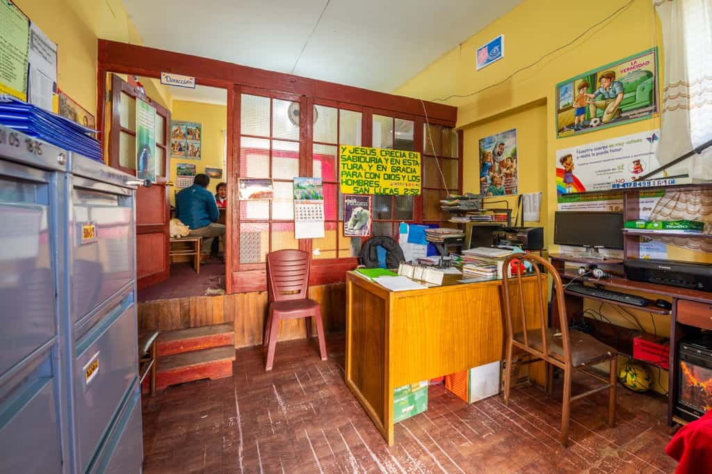 Inside an office with yellow walls at a Compassion center. There are filing cabinets and a desk.