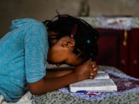 a girl wearing a blue shirt prays over an open Bible