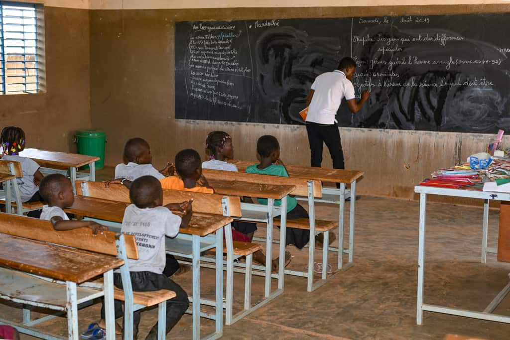 Man wearing a white polo shirt writing on a chalkboard with children at desks watching.