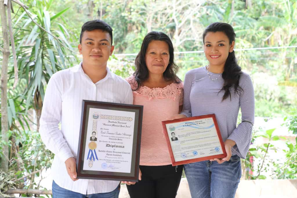 Erick, wearing a white striped shirt and jeans, is standing with his mother, Teresa, wearing a pink shirt and black pants, and his sister, wearing jeans and a purple shirt. Erick and his sister are holding Erick's diplomas. There are trees in the background.