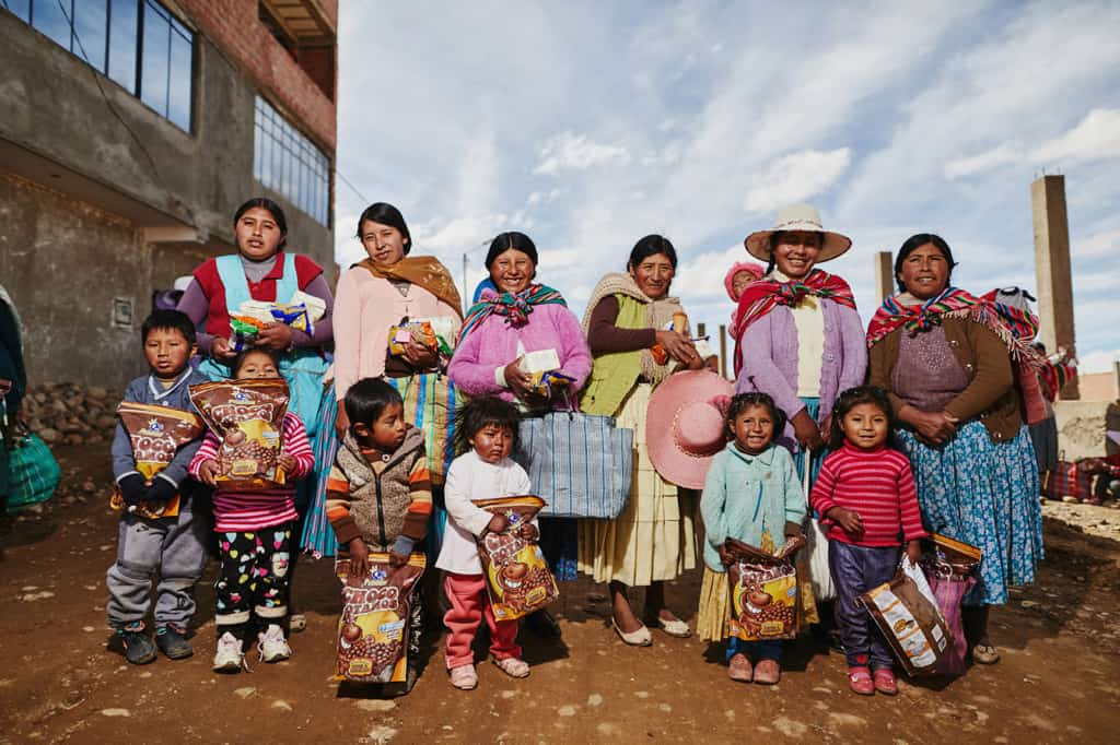 A group of mothers wearing blue, pink, green, purple and brown sweaters, and children stand on a dirt road holding bags of food. They are posing for a picture next to a building.