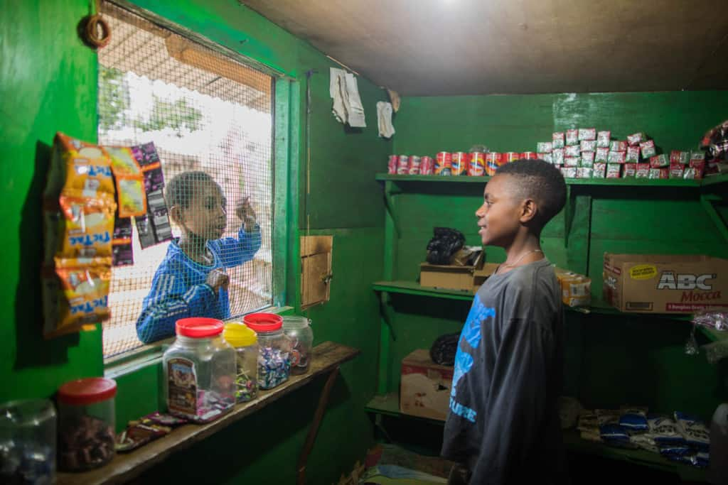 Petro is serving one of his customers who came to his green stall. The customers will usually order through the wire window. The items and change will be delivered through a small square hole.