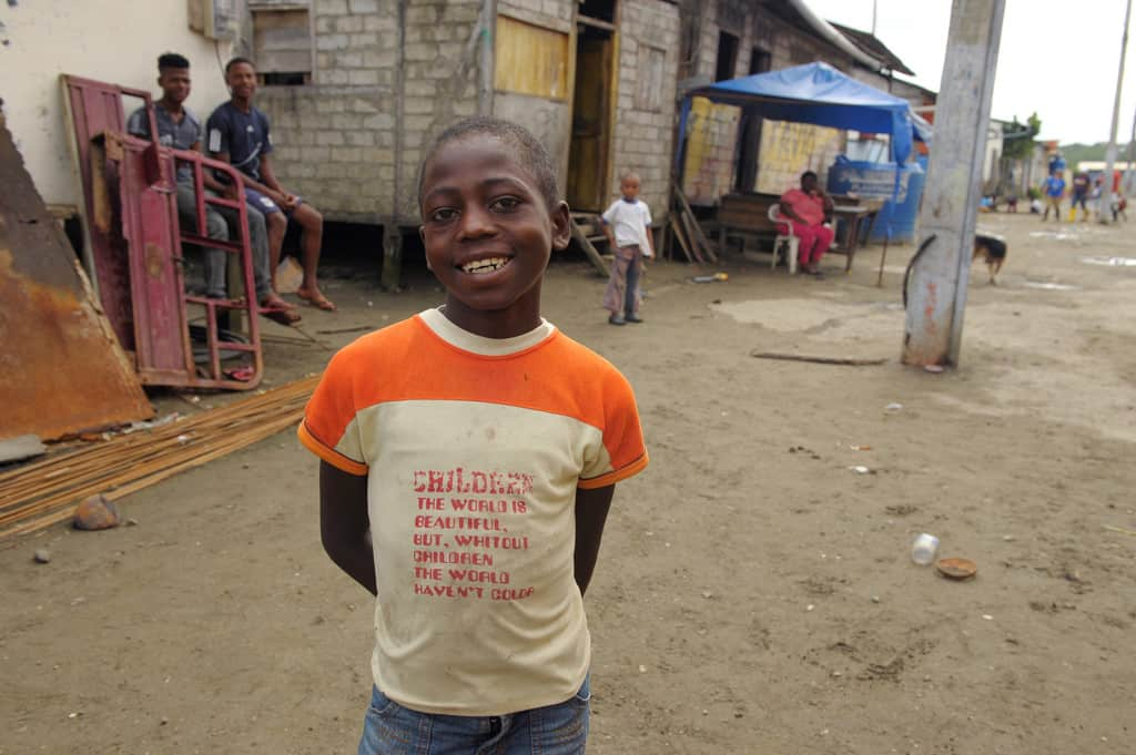 Boy wearing a white and orange shirt. He has a big smile and is standing on a dirt road.