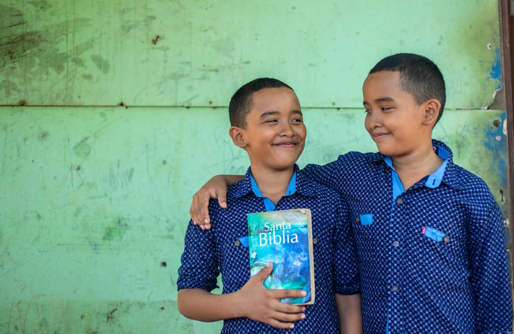 Twin boys wearing blue shirts and black pants. They are standing in front of their home and one is holding a Bible. The other has his arm around his brother.