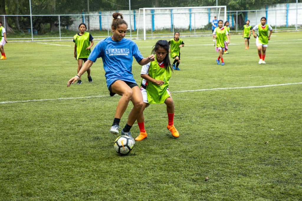 A woman in a blue Team Up with Compassion shirt is playing soccer with a ball on a field with girls in red and white uniforms covered with green pinnies.